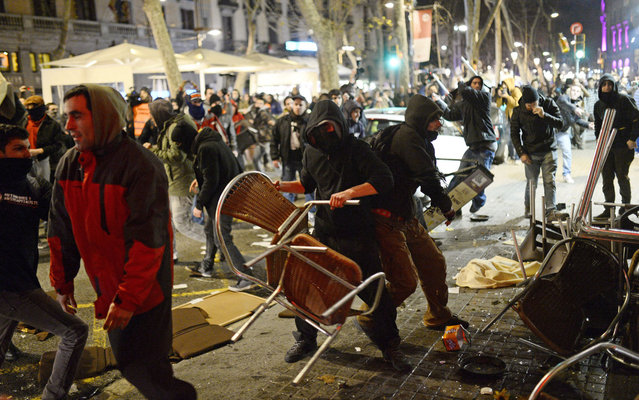 Protesters clash with policemen in Barcelona, Spain, Friday, January 17, 2014, as they clash during a demonstration to support the Gamonal neighborhood in Burgos where residents have protested tirelessly against the boulevard that the city wants to build there. (Photo by Manu Fernandez/AP Photo)