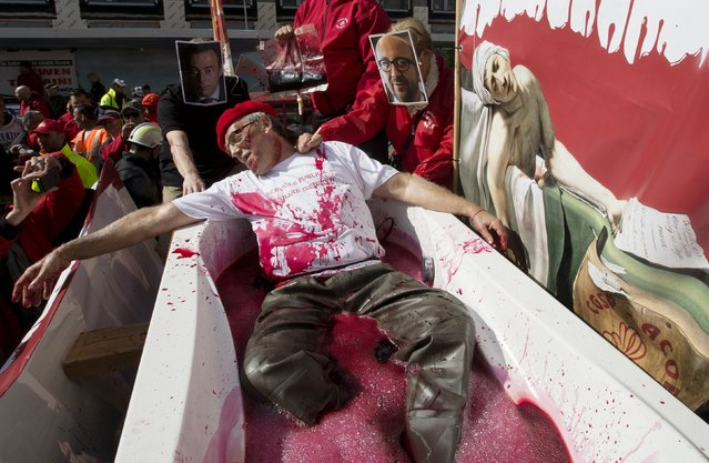 "A demonstrator lays in a bathtub filled with fake blood next to a placard reading ""Stop the social blood bath"" during a demonstration outside the Belgian Prime Minister's office in Brussels April 22, 2015. A public sector strike in Belgium disrupted high-speed rail services to Britain, France, Germany and the Netherlands as well as public transport across the country on Wednesday. (Photo by Yves Herman/Reuters)"