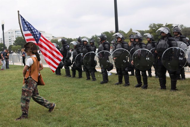 A demonstrator carrying a U.S flag passes by police officers standing in formation during a rally in support of defendants being prosecuted in the January 6 attack on the U.S. Capitol, in Washington, D.C., U.S., September 18, 2021. (Photo by Leah Millis/Reuters)