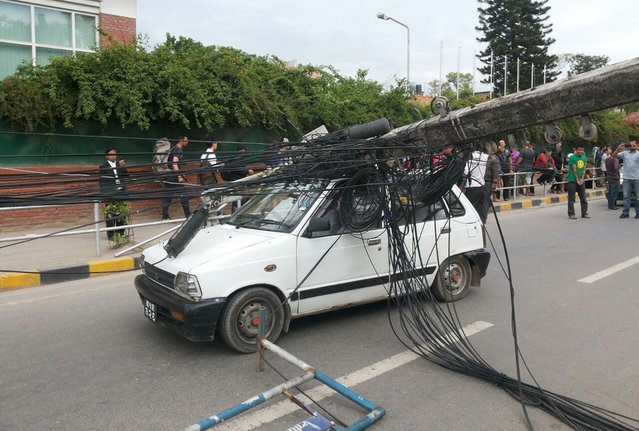 A car stands under the weight of an electric pole after it collapsed following an earthquake in Kathmandu, Nepal, Saturday, April 25, 2015. A strong magnitude-7.9 earthquake shook Nepal's capital and the densely populated Kathmandu Valley before noon Saturday, causing extensive damage with toppled walls and collapsed buildings, officials said. (Photo by Tashi Sherpa/AP Photo)