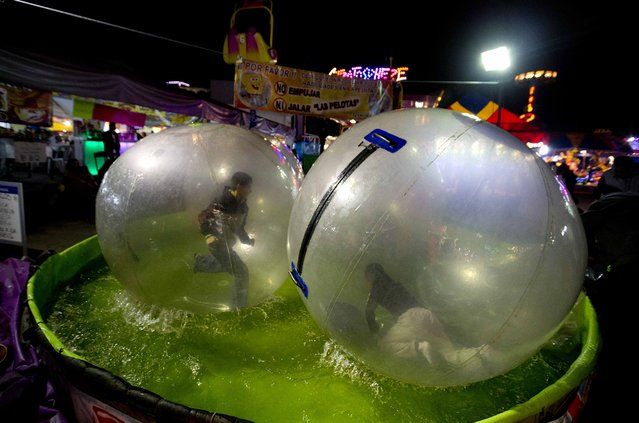 In this April 11, 2015 photo, kids play inside plastic bubbles floating on a pool at the Texcoco Fair on the outskirts of Mexico City. In Mexico, these types of fairs date back to Spanish colonial times, and in some smaller communities they are organized around the feast days of Roman Catholic saints. (Photo by Eduardo Verdugo/AP Photo)