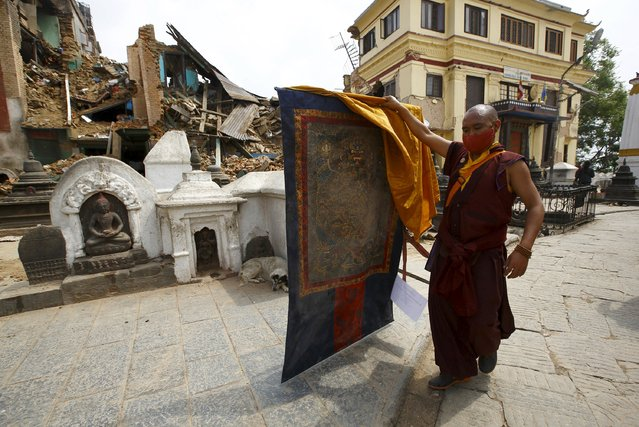 """A monk holding a """"Thanka"""", traditional Tibetan painting, walks out from the damaged monastery at Swoyambhunath Stupa, a UNESCO world heritage site, after Saturday's earthquake in Kathmandu, Nepal April 28, 2015. (Photo by Navesh Chitrakar/Reuters)"""