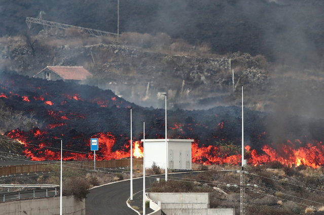 Lava rolls down behind street light posts in Los Llanos as the Cumbre Vieja volcano continues to erupt on the Canary Island of La Palma, as seen from Tajuya, Spain, October 13, 2021. (Photo by Sergio Perez/Reuters)