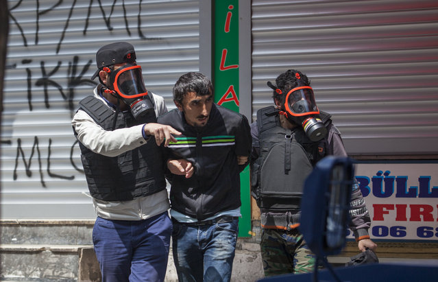 Police officers in gas masks detain a protester during clashes in Okmeydani neighbourhood in Istanbul, Turkey, May 1, 2015. (Photo by Kemal Aslan/Reuters)
