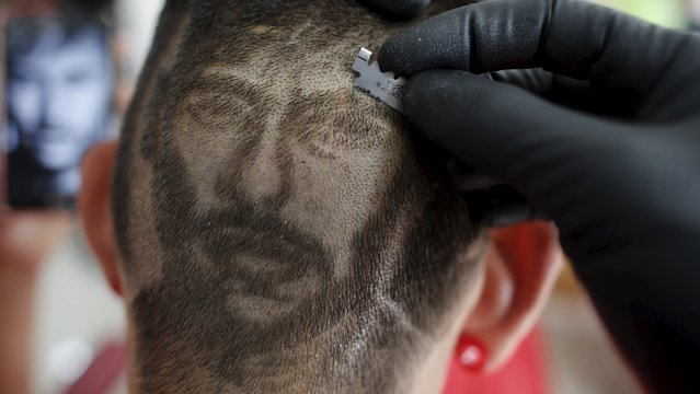 Hair artist and barber Nariko, 27, etches an image of Barcelona's Neymar on the head of customer Luiz Fernadez, 15, before the Champions League semifinal first leg soccer match between Barcelona and Bayern Munich at his barbershop in Sao Vicente, near Santos, in Sao Paulo state May 6, 2015. (Photo by Nacho Doce/Reuters)