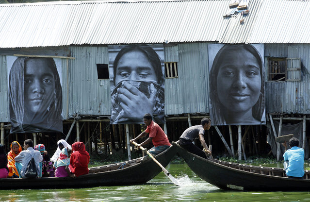 Boats carrying slum dwellers pass photographs of garment workers by the waterfront of Korail slum at Gulshan area in Dhaka, Bangladesh September 13, 2013. (Photo by Andrew Biraj/Reuters)