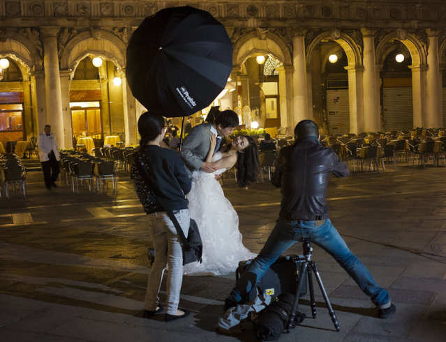 A Chinese just married couple poses for pictures in St. Mark's Square in Venice, Italy, Monday, May 4, 2015. (Photo by Domenico Stinellis/AP Photo)