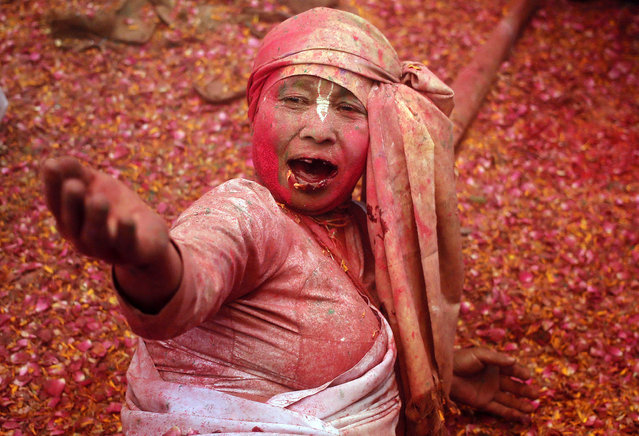 A widow daubed in colours sings religious songs as she takes part in the Holi celebrations organised by non-governmental organisation Sulabh International at a temple at Vrindavan, in the northern state of Uttar Pradesh, India, March 21, 2016. (Photo by Anindito Mukherjee/Reuters)