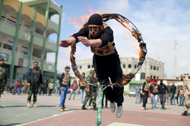 A Palestinian student jumps through a fire ring during a military-style show at a school in Rafah in the southern Gaza Strip March 28, 2016. (Photo by Ibraheem Abu Mustafa/Reuters)