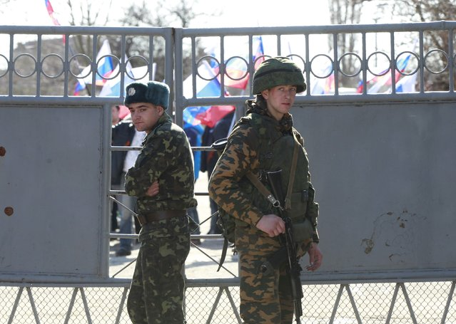 A Ukrainian serviceman (L) stands next to an armed man, believed to be a Russian soldier, inside a Ukrainian military base in the Crimean town of Yevpatoria, March 5, 2014. The United States and Britain failed in an attempt to bring Russia and Ukraine together on Wednesday at a meeting in Paris of a group created to assure Kiev's security after it renounced nuclear weapons in the 1990s. (Photo by David Mdzinarishvili/Reuters)