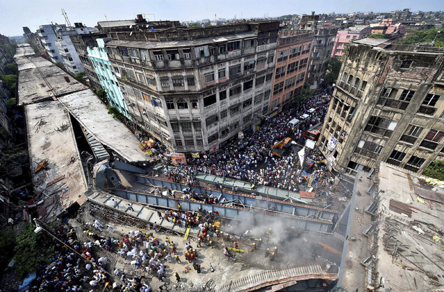 Locals and rescue workers clear the rubbles of a partially collapsed overpass in Kolkata, Thursday, March 31, 2016. Rescuers dug through large chunks of debris from an overpass that collapsed while under construction Thursday, killing many people and injuring scores of others, officials said. (Photo by Swapan Mahapatra/Press Trust of India via AP Photo)