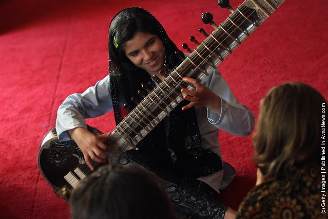Houma Rahimi, 12, plays the sitar during music class at a USAID-funded after school program for children affected by the Afghan war