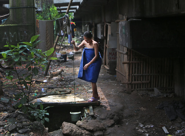 An Indonesian woman collects water for her shower from a well at a slum under a flyover in Jakarta, Indonesia, Thursday, March 13, 2014. Endemic poverty in the country of more than 240 million people remains a major problem and is expected to be a key issue in the presidential election that will be held later this year. (Photo by Tatan Syuflana/AP Photo)