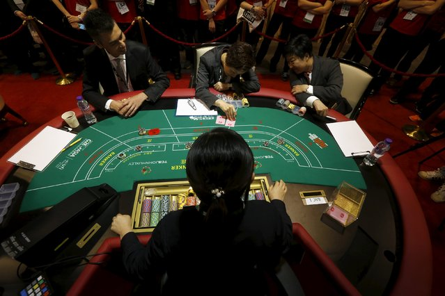 """Judges check a card as a contestant takes part in an """"All Asia Dealers Championship"""" at the Global Gaming Expo (G2E) Asia in Macau, China May 19, 2015. (Photo by Bobby Yip/Reuters)"""
