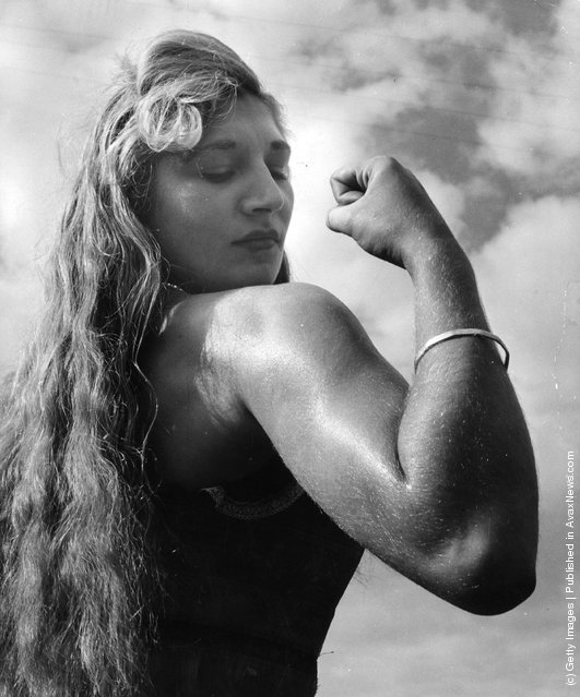 1953: Twenty-one year old Alice Penfold, a professional strong woman from Bury, near Pulborough, Sussex, flexes her biceps