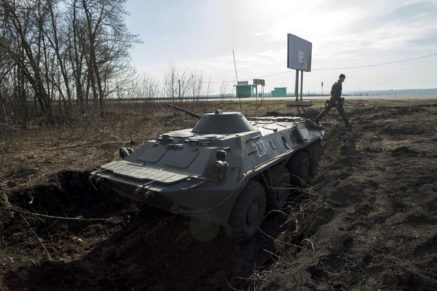 A soldier walks near an armoured personnel carrier in position close to the Russian border near the Ukrainian city of Kharkiv March 24, 2014. (Photo by Dmitry Neymyrok/Reuters)