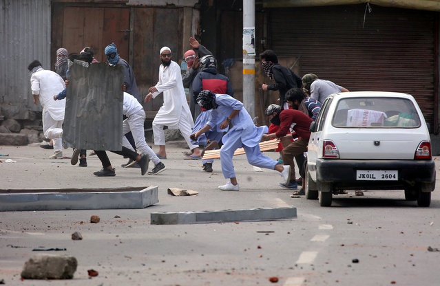 Kashmiri demonstrators run for cover as Indian police (unseen) chase them during a protest after Jumat-ul-Vida or the last Friday prayers of the holy fasting month of Ramadan, in Srinagar on May 31, 2019. (Photo by Danish Ismail/Reuters)
