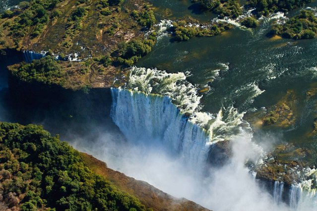 Victoria Falls (Zimbabwe/Zambia). Explorer David Livingstone named the waterfalls of the Zambezi River after Queen Victoria, but locals call them Mosi-oa-Tunya, meaning 'the smoke that thunders'. Located on the border between Zimbabwe and Zambia, the falls plummet 108m, creating a mist that is visible from 20km away. The falls were formed some 200-150 million years ago, during the Jurassic or Upper Karoo Period when land masses forming South America, African, India, Australasia and Antarctica were one huge super-continent known as Gondwanaland. (Photo by Kelly Cheng Travel Photography/Getty Images)