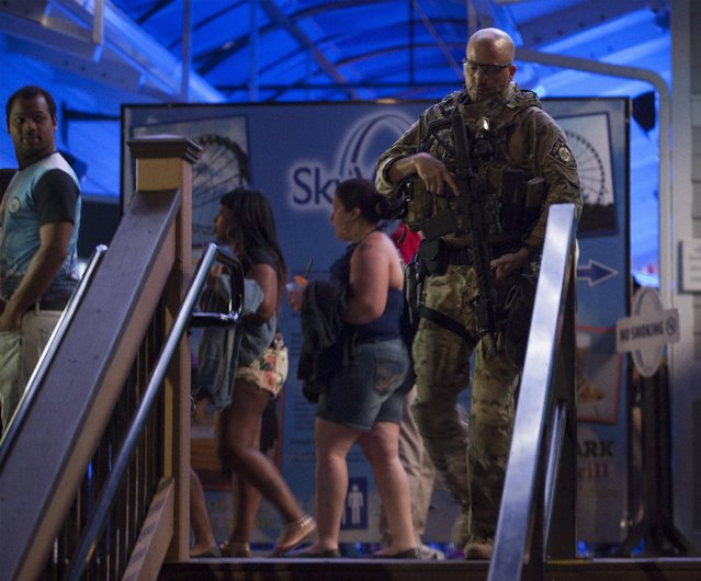 A member of an area SWAT team checks the Myrtle Beach SkyWheel responding to a call that a tourist yielded a gun on Ocean Boulevard during the 2015 Atlantic Beach Memorial Day BikeFest in Myrtle Beach, South Carolina May 24, 2015. (Photo by Randall Hill/Reuters)