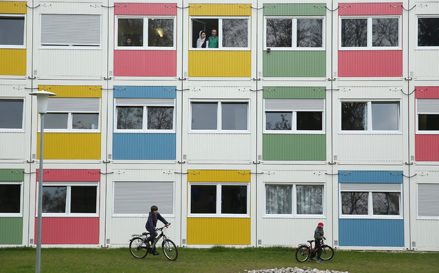 Children play as residents look from their window at the container settlement shelter for refugees and migrants in Zehlendorf district on April 14, 2016 in Berlin, Germany. Locals, many of them retirees, come to the shelter regularly to help the refugees and migrants, who are from countries including Syria, Iraq, Afghanistan, Kosovo and Serbia. The coalition partners of the German government yesterday announced a new package of legislation that includes measures to foster the integration of refugees who have received asylum status in Germany. (Photo by Sean Gallup/Getty Images)