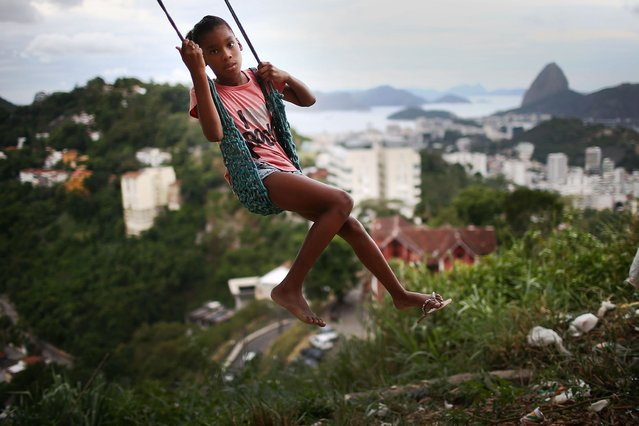 A child plays on a swing in the Prazeres pacified favela community on March 22, 2014 in Rio de Janeiro, Brazil. The favela was previously controlled by drug traffickers but is now occupied by the city's Police Pacification Unit (UPP). A number of UPPs were attacked by drug gang members on March 20, prompting some pacified favelas to soon receive federal forces as reinforcements. (Photo by Mario Tama/Getty Images)