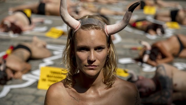 """An animal rights activist takes part in a protest ahead of the San Fermin Running of the Bulls at Plaza Consistorial on July 05, 2019 in Pamplona, Spain. Animal rights organizations, People for the Ethical Treatment of Animals (PETA) and Anima Naturalis, organised a creative interpretation of a violence-free San Fermin festival as they call for the abolition of bullfighting. Protesters wearing fake horns and a """"banderilla"""" (the bullfighter's colorful stick) on their back laid on the ground inside the outline of a bull. (Photo by Pablo Blazquez Dominguez/Getty Images)"""