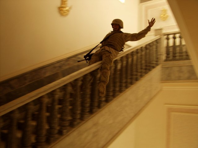A U.S. Marine slides down the marble bannister in Saddam's palace in Tikrit, Iraq, April, 2003. Tikrit was the last major city in Iraq to fall, and many people believed it symbolized the end of the fighting in Iraq. (Photo by Ashley Gilbertson/VII Photo Agency)