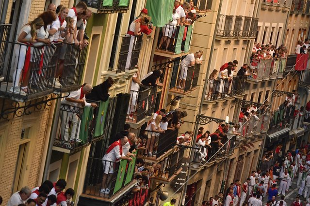 Revellers wait for the start of the running of the during the running of the bulls at the San Fermin Festival, in Pamplona, northern Spain, Friday, July 12, 2019. Revellers from around the world flock to Pamplona every year to take part in the eight days of the running of the bulls. (Photo by Alvaro Barrientos/AP Photo)