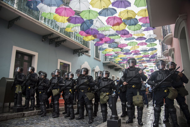 Police block protesters from advancing to La Fortaleza governor's residence in San Juan, Puerto Rico, Sunday, July 14, 2019. Protesters are demanding Gov. Ricardo Rosselló step down for his involvement in a private chat in which he used profanities to describe an ex-New York City councilwoman and a federal control board overseeing the island's finance. (Photo by Carlos Giusti/AP Photo)