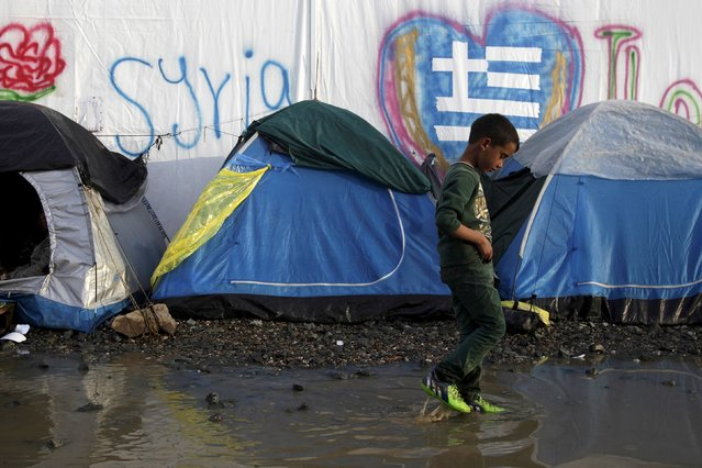 A boy walks in a puddle next to tents following heavy rainfall at a makeshift camp for migrants and refugees at the Greek-Macedonian border near the village of Idomeni, Greece, April 24, 2016. (Photo by Alexandros Avramidis/Reuters)