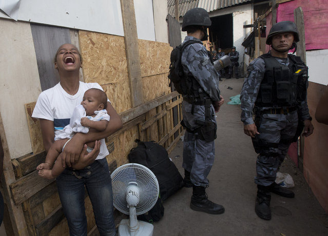 A woman carrying a baby, reacts during an eviction in Rio de Janeiro, Brazil, Friday, April 11, 2014. Squatters in Rio de Janeiro are clashing with police after a Brazilian court ordered that 5,000 people be evicted from abandoned buildings of a telecommunications company. Officers have used tear gas and stun grenades to try to disperse the families. (Photo by Silvia Izquierdo/AP Photo)