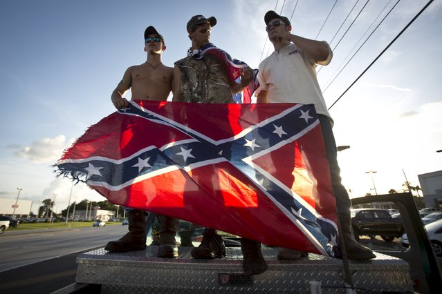 "Participants in the ""Ride for Pride"" event stand on the back of their pickup truck as they take part in an impromptu event to show their support for the Confederate flag in Brandon, Hillsborough County, June 26, 2015. Several hundred people took part in the event. (Photo by Carlo Allegri/Reuters)"