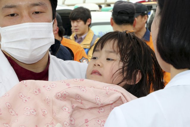 """A girl rescued by South Korean maritime policemen from a sinking ship """"Sewol"""" in the sea off Jindo, is treated at a port in Jindo April 16, 2014. (Photo by Hyung Min-woo/Reuters/Yonhap)"""