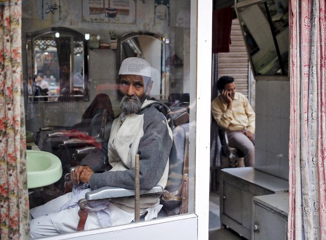 A man waits to get his beard trimmed inside a barber shop as another speaks on his mobile phone in the old quarters of Delhi in this November 12, 2014 file photo. India is expected to release services PMI data this week. (Photo by Anindito Mukherjee/Reuters)
