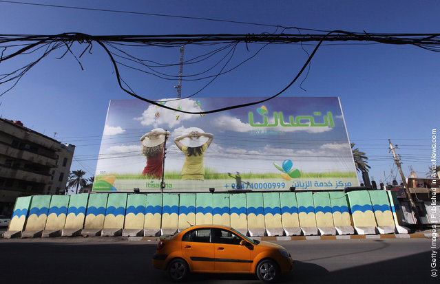 An advertisement for mobile telephone service is seen behind painted protective blast walls