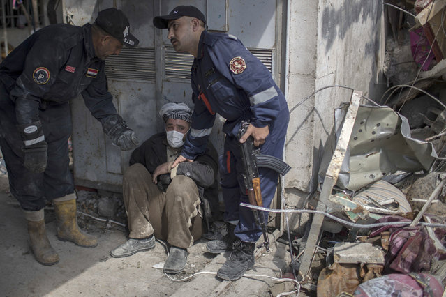 A man is helped after identifying the body of a relative who died in a house that was destroyed during fights between Iraq security forces and the Islamic State on the western side of Mosul, Iraq, Friday, March 24, 2017. Residents of the Iraqi city's neighborhood known as Mosul Jidideh at the scene say that scores of residents are believed to have been killed by airstrikes that hit a cluster of homes in the area earlier this month. (Photo by Felipe Dana/AP Photo)