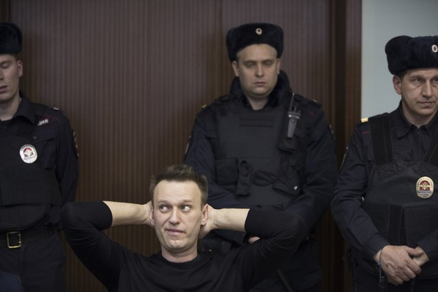 Russian opposition leader Alexei Navalny, foreground left, waits to hear a sentence in court in Moscow, Russia, Thursday, March 30, 2017. Many Western countries have condemned the arrests and called for the release of those sentenced to jail, including opposition leader Alexei Navalny, Putin's most prominent foe. (Photo by Pavel Golovkin/AP Photo)