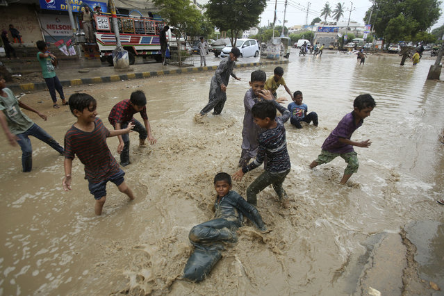 Pakistani boys play in a flooded street after a heavy rainfall in Karachi, Pakistan, Monday, July 29, 2019. The Pakistan Meteorological Department said that a rain system entered Sindh province from India's Rajasthan and forecasts another three days of rain. (Photo by Fareed Khan/AP Photo)