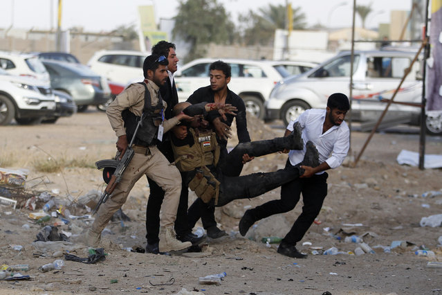 Men evacuate an injured person after a car bomb attack at a Shi'ite political organisation's rally in Baghdad, April 25, 2014. (Photo by Thaier al-Sudani/Reuters)