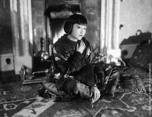 1928: American-Chinese actress Anna May Wong (1907 - 1961) sitting on the floor wearing a wrap