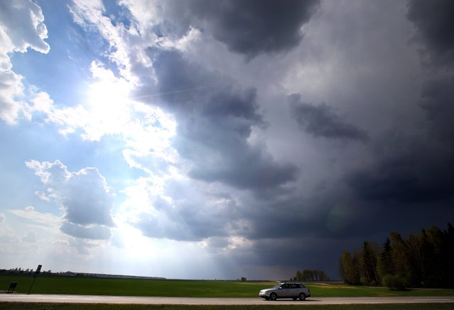 A car on a road appears to move from thunderstorm (R) to sunshine (L) as it drives near the village of Korma, some 30 kilometers from Minsk, Belarus, 22 April 2014. Temperatures reached up to 21 degrees Celsius in the Minsk region on 22 April, exceeding the normal climatic temperature of 5 to 10 degrees Celsius, local media reported. (Photo by Tatyana Zenkovich/EPA)
