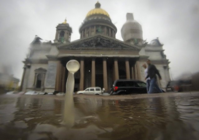 Raindrops fall into a puddle in St.Petersburg, Russia, Tuesday, July 7, 2015, with the city's landmark St. Isaac's Cathedral in the background.  Cyclone from the west brought rains to St. Petersburg on Tuesday. (Photo by Dmitry Lovetsky/AP Photo)