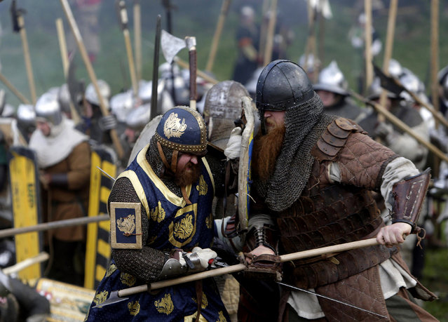 Enthusiasts wearing medieval knight costumes fight during a battle in the central Bohemian village of Libusin April 26, 2014. Some two thousand participants took part in an annual re-enactment of the battle of Libusin. (Photo by David W. Cerny/Reuters)
