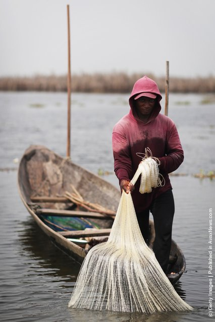 A man casts a net while fishing in the lagoon on his boat near Ganvie, Benin