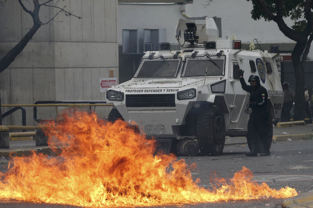 A police officer guides an armored vehicle during clashes with anti-government protesters in Caracas, Venezuela, Wednesday, April 19, 2017. (Photo by Fernando Llano/AP Photo)