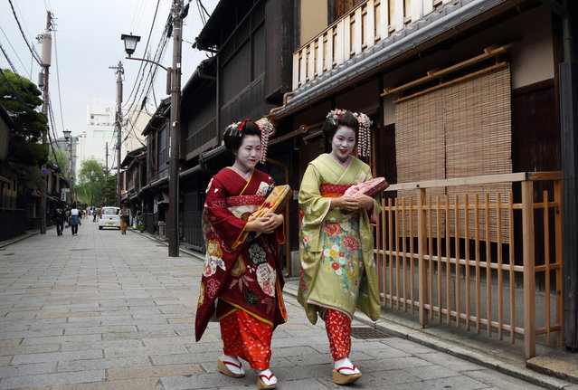 Tourists wearing rental traditional kimonos for maiko, an apprentice geisha, walk through the Gion area of Kyoto, Japan, on Saturday, May 3, 2014. (Photo by Tomohiro Ohsumi/Bloomberg)