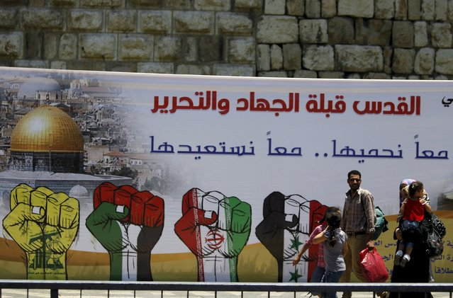 "People walk past a billboard erected to mark the annual al-Quds Day, or Jerusalem Day, on the last Friday of the Muslim holy month of Ramadan in Damascus, Syria July 10, 2015. The billboard reads in Arabic, ""Al Quds is the compass for jihad and liberation"". (Photo by Omar Sanadiki/Reuters)"