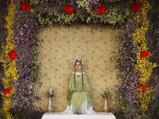 """A """"Maya"""" girl sits in an altar during the traditional celebration of """"Las Mayas"""" on the streets in Colmenar Viejo, near Madrid, Spain, Friday, May 2, 2014. (Photo by Daniel Ochoa de Olza/AP Photo)"""