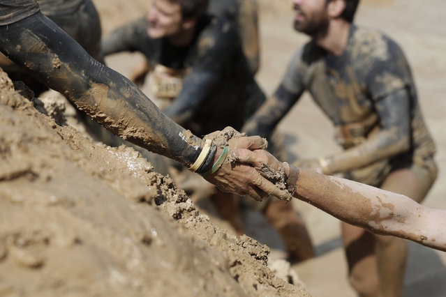 A participant assists another up a hill during the Mud Day Paris 2017 obstacle course in Beynes on April 29, 2017. (Photo by Thomas Samson/AFP Photo)