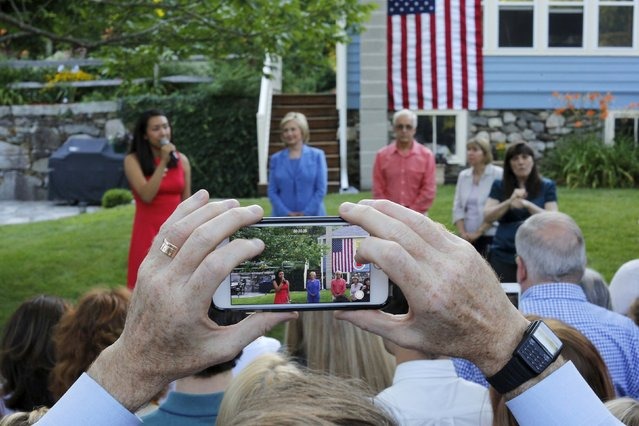 An audience member makes a video with a mobile phone as Democratic presidential candidate Hillary Clinton is introduced during a campaign stop in a back yard of a home in Windham, New Hampshire July 16, 2015. (Photo by Brian Snyder/Reuters)